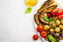 Grilled Vegetables And Mushrooms On Plate Over White Background, Top View