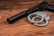 A Pistol With A Silencer And Handcuffs On The Table. Catching Arrest Of A Criminal, Prison. Killer