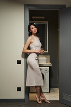 Beautiful Graceful Slender Young Woman In A Tight Light Dress Stands In The Doorway To The Bathroom With A Glass Of Water
