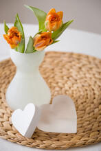 Top View Of A Frosted Glass Vase With Beautiful Spring Tulips And Two Hearts Lying On A Straw Background. Easter And The Beginning Of Spring Concept