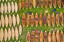 Aerial View Of A Few People Working On Repairing Small Wooden Fishing Boat In Ghior Central Playground, Ghior, Dhaka, Bangladesh.