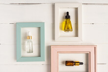 White, Ellow And Brown Glass Bottles With Serum, Essential Oil Or Other Cosmetic Product In Frames On Wooden Background. Natural Organic Beauty Cosmetic Concept.