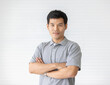 Portrait close up shot of handsome asian male model with short black hair wearing gray polo shirt stand smiling in front of white background