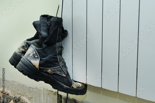 Obraz Old dirty ragged builders boots hangs on lace at construction site - fototapety do salonu