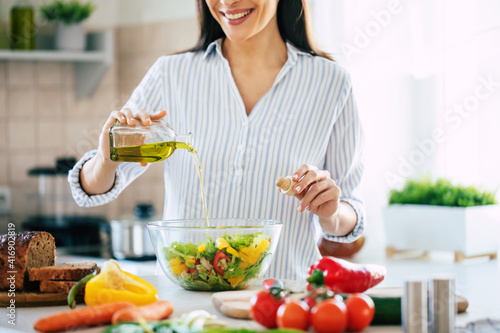 Fotografie, Obraz Close up photo of a smiling young woman makes a fresh vegan salad while she uses olive oil for it
