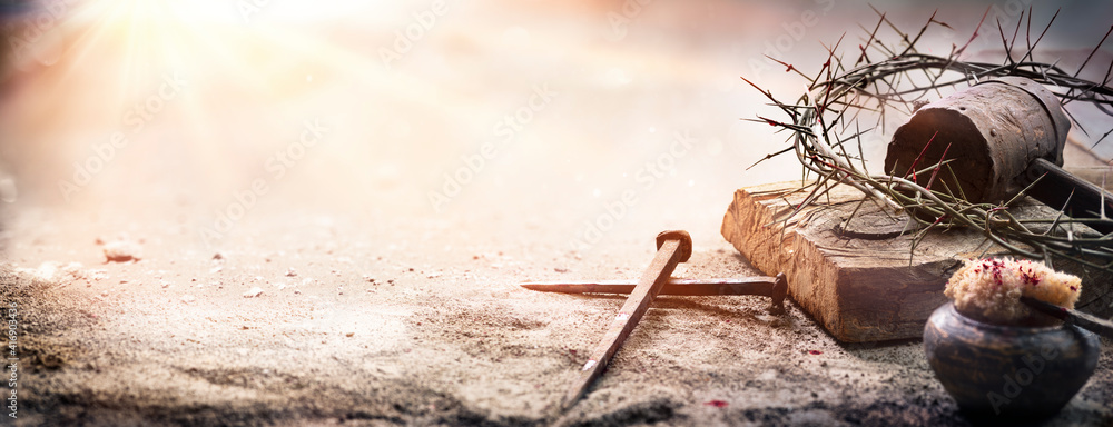 Fototapeta Passion Of Jesus Christ - Hammer And Bloody Nails And Crown Of Thorns On Arid Ground With Defocused Background