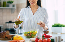 Close Up Photo Of A Smiling Young Woman Makes A Fresh Vegan Salad While She Uses Olive Oil For It.