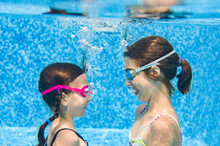 Children Swim In Swimming Pool Underwater, Little Active Girls Have Fun Under Water, Kids Fitness And Sport On Family Vacation