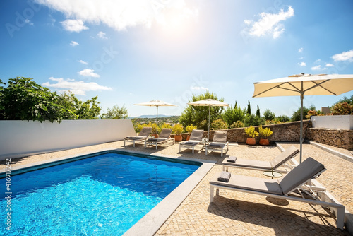 Fotografie, Obraz Loungers placed on the right and in the front of a pool with clean looking water on a sunny day