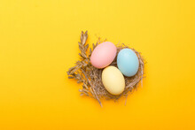 Close Up Photo Of Birds Nest Easter Eggs Over Yellow Background.