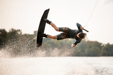 Active Male Wakeboarder Doing Somersault In The Air Above Water