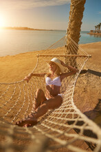 Travel And Vacation Concept - Woman Relaxing On Hammock On The Beach