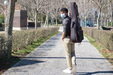 Latin Young Man Wearing Protective Face Mask Carrying A Guitar In A Guitar Case On A City Street. University Campus.