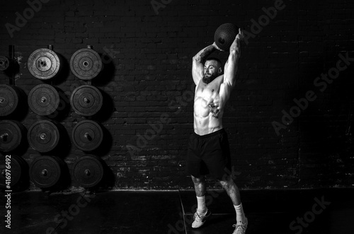 Vászonkép Young sweaty strong muscular fit man with big muscles doing ball throwing on the