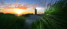 Lighthouse With Beacon On Coast In Windy Sea With Dunes And Grass