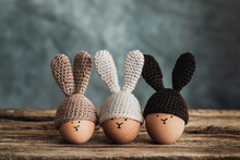 Three Easter Eggs In Crochet Hats With Bunny Ears On Old Wooden Table
