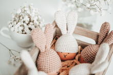 Cute Easter Eggs In Crocheted Hats With Bunny Ears In A Wooden Box On The Table Home Happy Easter Decoration Concept.