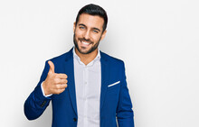 Young Hispanic Man Wearing Business Jacket Doing Happy Thumbs Up Gesture With Hand. Approving Expression Looking At The Camera Showing Success.
