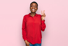 Young African American Woman Wearing Casual Clothes And Glasses Smiling With Happy Face Winking At The Camera Doing Victory Sign. Number Two.