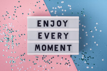 Enjoy Every Moment - Text On Display Lightbox On Blue And Pink Background.