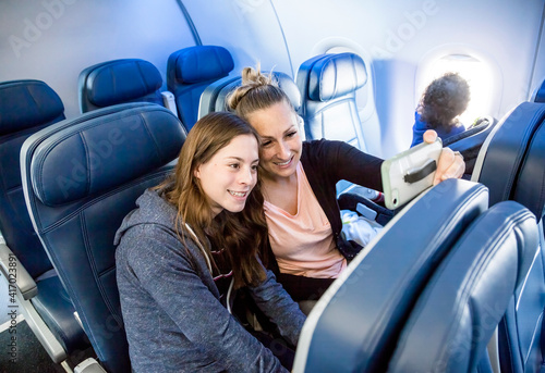 Obraz Two women taking a selfie together while traveling on an airplane. A mother and daughter sitting on an airplane and excited about their upcoming vacation. Smiling happy faces - fototapety do salonu