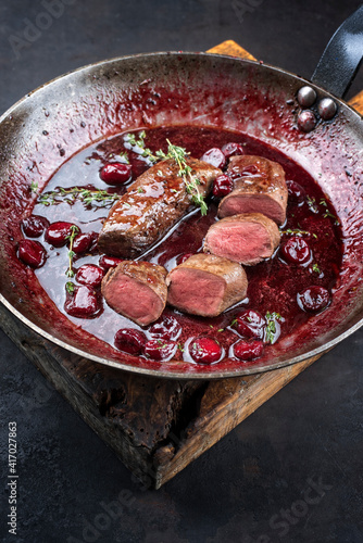 Fototapeta Traditional wild hare back filet braised with wild berries and cherry relish souse served as close-up in rustic frying pan on an old wooden board obraz