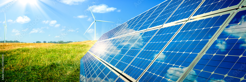 Fototapeta Solar Panels And Wind Turbines In Grassy Field With Sunlight - Renewable Energy Concept