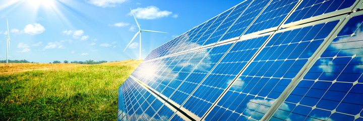Solar Panels And Wind Turbines In Grassy Field With Sunlight - Renewable Energy Concept