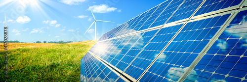 Solar Panels And Wind Turbines In Grassy Field With Sunlight - Renewable Energy Concept #417028878