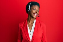 Young African American Girl Wearing Call Center Agent Headset Looking Away To Side With Smile On Face, Natural Expression. Laughing Confident.