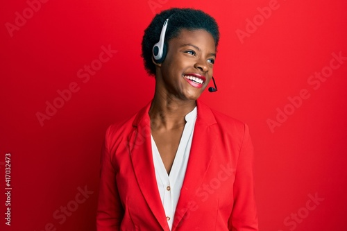 Fotografía Young african american girl wearing call center agent headset looking away to side with smile on face, natural expression