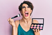 Young Man Wearing Woman Make Up Holding Makeup Brush And Blush Angry And Mad Screaming Frustrated And Furious, Shouting With Anger Looking Up.
