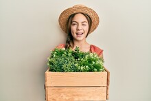 Beautiful Brunette Little Girl Wearing Gardener Hat Holding Wooden Plant Pot Winking Looking At The Camera With Sexy Expression, Cheerful And Happy Face.