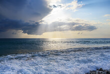 The Sun's Rays Make Their Way Through A Hole In The Cloud And Fall On The Sea. There Is A Lot Of Foam On The Shore From The Oncoming Waves. Summer Seascape