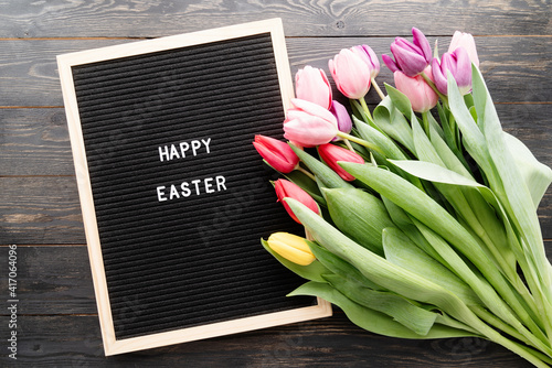 Bouquet of colorful tulip flowers and letter board with the words Happy Easter t Fototapet
