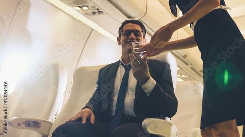 Fotografie, Obraz Cabin crew serve water to passenger in airplane