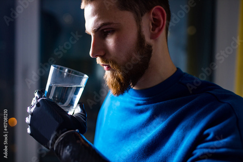 Foto young man with modern biotechnology hand in apartment holding water glass