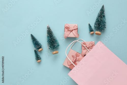 Fototapeta Shopping package with mini Christmas trees, gift boxes on blue background. Christmas shopping obraz