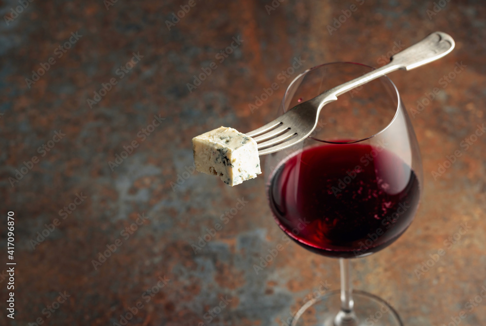 Fototapeta Blue cheese on a fork and red wine.