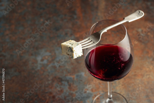 Blue cheese on a fork and red wine. © Igor Normann