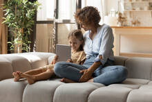 Close Relationship. Affectionate Young Mother Embrace Little Girl Sit On Sofa Use Pad Shopping At Web. Happy Family Of Two Single Mom And Daughter Kid Relax At Home Together Chat Check Social Networks