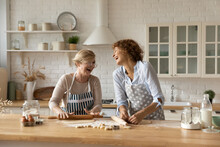 Warm Relations. Happy Old Woman Mother Pensioner Young Female Daughter Grown Up Kid Engaged In Baking Cookies Roll Dough At Kitchen Together Laugh Have Fun. Elderly Lady Enjoy Cooking With Adult Child