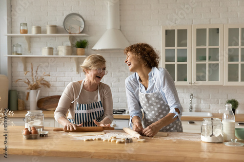 Warm relations. Happy old woman mother pensioner young female daughter grown up kid engaged in baking cookies roll dough at kitchen together laugh have fun. Elderly lady enjoy cooking with adult child © fizkes