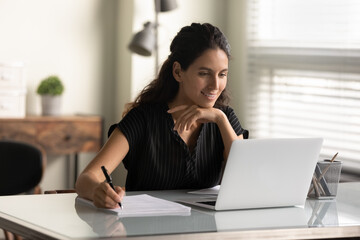 Smiling woman looking at laptop screen, watching webinar or lecture, online course, taking notes, sitting at desk, motivated young female student studying, businesswoman freelancer working on project