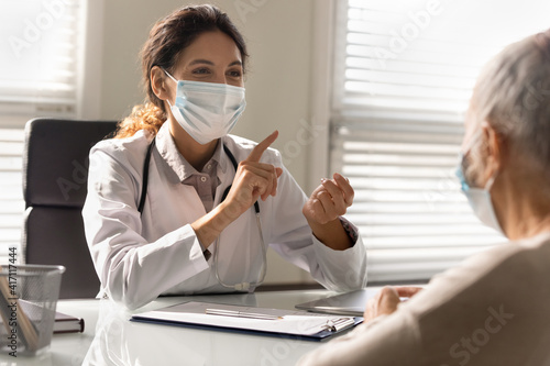 Leinwand Poster Close up smiling female doctor wearing medical face mask consulting mature patie