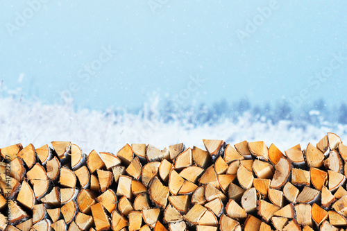 Photo Woodpile of firewood on the background of a winter landscape