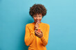 canvas print picture - Happy surprised Afro American woman browses internet and networking in social media tests new application for smartphone wears casual jumper isolated over blue background. Mobile communication