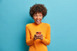 canvas print picture - Positive curly haired ethnic woman uses mobile phone checks messages and reads news holds modern cellular in hands looks with curious happy expression on right isolated over blue background.
