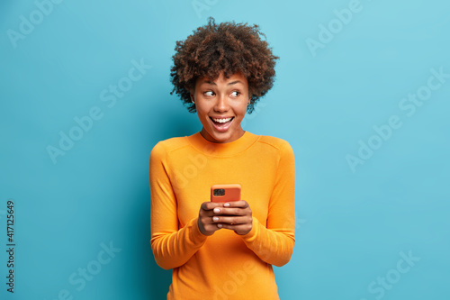 Positive curly haired ethnic woman uses mobile phone checks messages and reads news holds modern cellular in hands looks with curious happy expression on right isolated over blue background.
