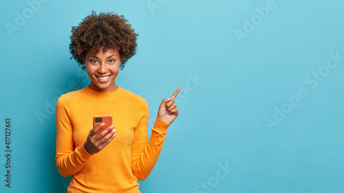 Obraz Horizontal shot of happy dark skinned Afro American woman enjoys mobile communication and modern technologies poses against blue background points away on free space for your advertising content - fototapety do salonu